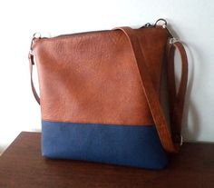 This cross-body / shoulder bag is handmade of distressed tan and blue vegan, faux leather. Perfect everyday bag. Closes with a zipper. The interior is fully lined. Measurements: 11 x 11 - adjustable and removable strap - two inside pockets - simple and trendy design - handmade Visit my shop for more items: http://www.etsy.com/shop/reabags Thanks for looking