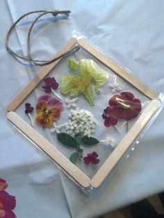 Flower sun catcher. Peel and stick laminate, craft sticks, flowers and twine.