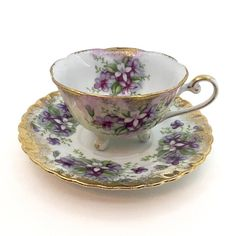 Beautiful Royal Sealy Tea Cup Set! This 3 footed cup and saucer set is covered with bouquets of violets and brushed gold around its scalloped edges. Saucer Measures: 5 3/4 in Cup Measures: 3 in Please note that all of my items are vintage, and therefore, not all are going to be