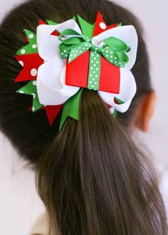 """This multi layered hair bow is about 4+"""""""" across and ready to accent any holiday outfit. Red polka dot and green polka dot ribbon flaring out around the bottom give it a fun look. The top layer has a"""
