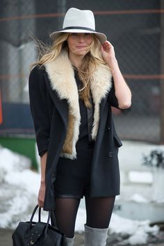Valentina Zelyaeva in a black coat + shearling vest + grey suede over-the-knee boots + wide-brim hat