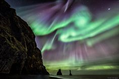 The Stars, Aurora and Legends collide in this dramatic vista of land, sea and sky. The land is Iceland, specifically Vík í Mýrdal, a southern village known for its beautiful black sand beaches. The sea, the Atlantic Ocean, surrounds Reynisdrangar, a sea stack of eroded basaltic rock pillars that Icelandic folklore tells are the petrified remains of trolls trying to lure sailing ships. Also watching from the sky are the Aurora, northern stars and the planet Jupiter. I Image by Elizabeth M…