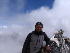 Mt. Everest is over his shoulder; climbing partner Ganesh stands on the summit of 19,000 ft. Pokalde Peak, Nepal Himalayas.