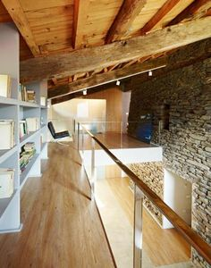 Love the clean lines and combination of materials: the stone and rough beams against the finished wood flooring, white-finished shelving, and glass 'railing'.