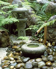 Japanese style water feature with bamboo spout and lantern in the background, UK