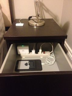 Put a power strip in the top drawer of your nightstand to charge/organize/hide your electronics.  Well, this is just genius