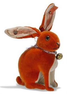 A STEIFF SAMPLE ORANGE VELVET RABBIT, (3415), seated, brown and black glass eyes, pink and black stitching, swivel head, wired ears, ribbon with bell, Muster button and FF button with red cloth tag with handwritten number, circa 1929 --5in. (18cm.) high (right ear with tear, some rusting to wire which has stained the ear and buttons a little rusty)