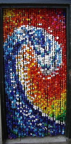 Repurposed plastic milk bottle caps and nylon fishing line create a doorway or wall hanging of giant surf. Rescue and recycle, upcycle, salvage! For ideas and goods shop at Estate ReSale & ReDesign, Bonita Springs, FL