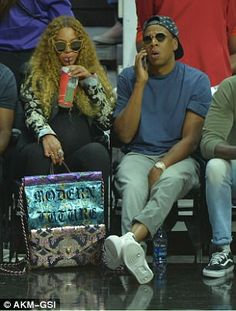 Play paused: During a break in the action, Beyonce sipped on a refreshing beverage while Jay Z chatted on his cell phone