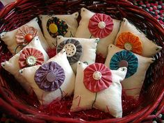 Miniature pillows decorated with flower yo-yo's; would be great as a scented pouch for lingerie drawer etc.