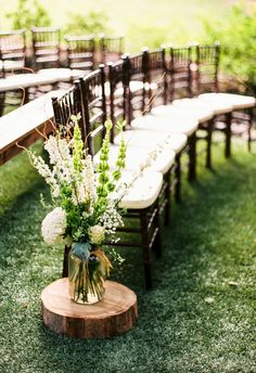 Yes to green and white florals atop tree trunk stumps lining the aisle // JoPhoto