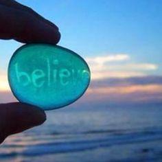 Believe [written on sea glass held up in front of the ocean]