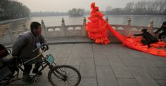 """The artist Kong Ning wore a costume made of hundreds of plastic trumpets in Beijing on Monday to call attention to the hazardous smog. Credit Damir Sagolj/Reuters.  Across Beijing, residents braced for another """"airpocalypse"""" — the term that some English speakers in the city use for the most toxic bouts of air pollution."""