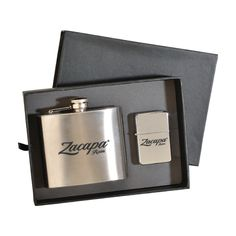 Deluxe 5 oz. Flask and Oil Flip Top Lighter Gift Set- Indulge your client's senses with this sophisticated gift set. Heavy duty cardboard gift box includes a stainless steel 5 oz. flask, flip top oil lighter, and imprinting on both items. 2 setup charges apply. For imprinting on gift box, please add 0.30/r and additional setup. #Flask #Lighter #OilFlipTopLighter #GiftBox