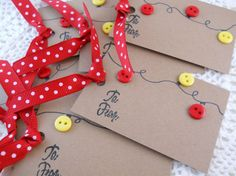 Christmas Lights Gift Tags - A set of 6 whimsical Christmas lights gift tags made from kraft cardstock. The string is hand drawn with ink and embellished with red and yellow buttons. Cards have a red and white dotted grosgrain ribbon and hand stamped with To From. The backs are blank. Each tag measures 2x 3. Tags will be shipped in a clear resealable zip bag. All my crafts are made in my smoke-free home. 100% of my profits go toward buying textbooks for deserving college students (who…