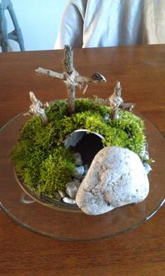 I made this pinterest inspired Easter center piece this morning! Messy, but easy-peasy. Put a cup on a nice platter. Filled with dirt, put rocks in the front, put down some moss (straight from my back yard) over the top of the tomb. Used sticks and twine to make crosses and a large rock to be rolled away! $0