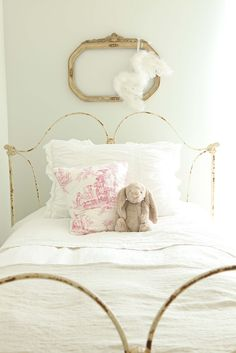 chippy vintage iron bed, teddy bear, old gold frame, white linens...I like this for Laylas room minus the wings hanging from the old frame:-P