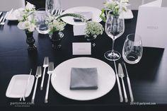 Feines Porzellan, ein stilvolles Besteck und eine zarte weiße Blume