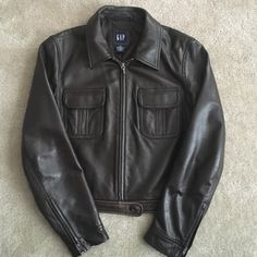 Gap Leather Jacket Women deep chocolate brown Gap Soft Leather Jacket. Zip front, stops at the waist. Zips on the sleeve. This jacket is in great condition considering it's age (almost 15 years old). Quality Leather!! The leather is worn a little at the bottom near the waist by the button but overall this jacket is in great shape.  Would be a keeper but I no longer can fit it. GAP Jackets & Coats