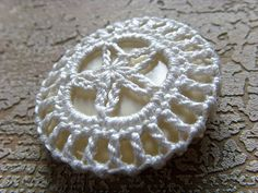 the starfish crochet button  --    http://mademoisellechaos.blogspot.com/2010/03/starfish-crochet-button.html