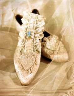 Lady Diana's wedding slippers and garter.  Celebrity cobbler Clive Shilton made her shoes.  Diana chose a heart shaped tab to decorate the front.