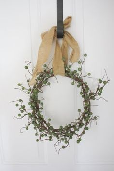 Made of dollar tree berries twisted into a circle & hung with burlap. Easy & simple decor