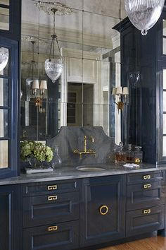 Gorgeous blue cabinetry, gold accents and mirrored wall via  Quintessential Kitchens