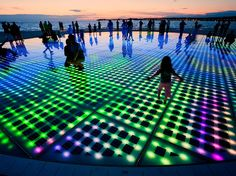 Nikola Bašić - Greetings to the Sun  This public art installation by Croatian architect Nikola Bašić comes to life at sunset in the beautiful coastal town of Zadar, Croatia. This circle of light consists of 300 photovoltaic solar glass plates installed on the stone-paved waterfront.  The LED's change color and pattern to create a spectacular show of light.