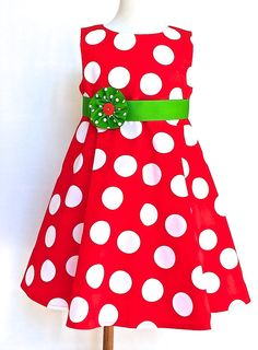 This red and white polka dot Christmas dress looks fabulous in photos, with its bright green belt and polka dot flower. Classic, simple styling with