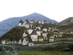 City of the Dead in Northern Ossetia, Russia.  In the remote, rugged Gizel valley of Northern Ossetia, Caucasus, Russia, there is a set of stone buildings that from a distance look like a regular village - but with one important detail: it is not for the living. A closer look inside the buildings with slanted slate roof reveal something gruesome: mummified bodies dressed in their best clothes and shoes with hair tidily combed.