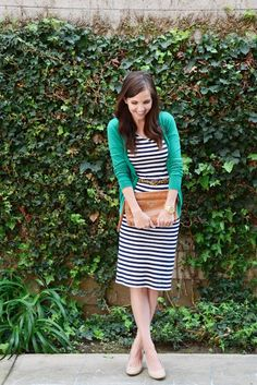 bright cardigan over a striped dress.