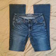 "Rue 21 Jeans 5/6 Cute medium/dark wash Rue 21 brand Jeans. Cute pockets with detailed stitching and button down pocket flaps. Mid-rise Boot cut.  These jeans are in terrific condition. No wear at all on the bottom pant cuffs!   Juniors size 5/6.  Inseam: 32"" Rue 21 Jeans Boot Cut"