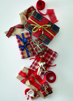 Get creative with your wrapping and look to your basket of fabric scraps or visit your local fabric store for whatever they have in their sale bin. Choose plaids in holiday colors and top them off with an equally interesting textured ribbon, such as raffia, chunky yarn or twine. Add a charming holiday ornament for a finishing decorative touch that keeps the seasonal theme.