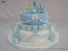 Boys Birthday Cake. A two tier boys birthday celebration cake in white and blue, featuring sugar modelled characters of teddy and blanket, train and ball. Finished with contrasting sugar ribbons, bows and named building blocks