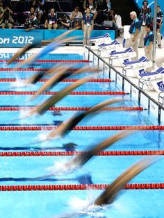 Swimmers dive into the pool in a women's 200-meter breaststroke swimming heat.