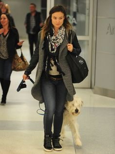 Olivia Wilde layered up in a cozy coat, sweater, and fringed scarf.
