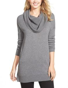 A face-framing cowl begins a cozy tunic sweater fashioned with dropped shoulders, ribbed sleeves and slits at the sides.