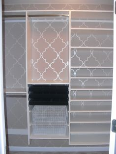 Small walk-in master closet transformed with custom built-ins and wall paper.
