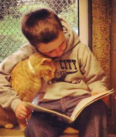 This kid reads with confidence when his cat pal is around.