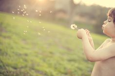 photo of a child blowing a dandelion. I'll bet it's hard to do, but I want to try it!