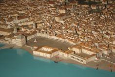 Recuemos até 31 de Outubro de 1755, véspera do sismo que arrasou Lisboa. Deambulemos pelo emaranhado de ruas sujas e nauseabundas, de traça medieval, e depois continuemos a pé até à beira do Tejo. Entre o labirinto de casas e ruelas desordenadas, abre-se o Terreiro do Paço, praça ampla com uma fonte no meio: de um dos lados, sobressai o torreão do Paço da Ribeira, onde vivem o rei e a corte. Não muito longe, encontramos a Igreja da Patriarcal, a recém-construída Ópera do Tejo ou a Ribeira…