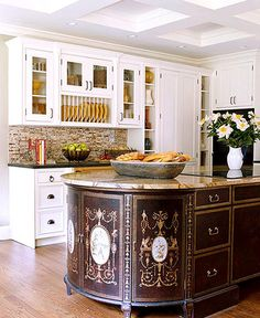 Chinoiserie chests unite to create a dramatic design statement in the form of a kitchen island. An oval-shape marble slab unites the two chests with a center cabinet that was stained and painted to match. - Traditional Home®