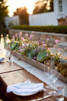 Un centrotavola con piante grasse e fiori