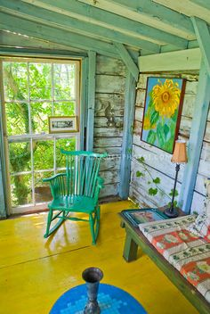 Porch of house with painted wood floor, bright colors, rustic eclectic furniture rocker, LOVE!