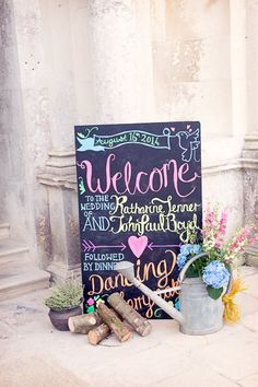 Brightly coloured chalkboard welcome sign - Image by One Thousand Words - Vintage YSL Skirt For A Colourful 20s Inspired Wedding At The Lulworth Estate Dorset With Groom In Moss Bros. Suit And Images By One Thousand Words Wedding Photographers