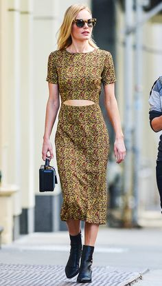 Kate Bosworth wears a printed midi dress, ankle boots, a mini top handle bag, and square sunglasses