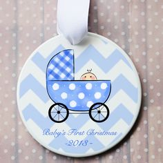 """Celebrate the arrival of your new bundle of joy with our babys first christmas ornament. Porcelain ornament features a blue baby buggy and a cute little face peeking out, professionally printed and heat set ornament with white grosgrain ribbon measures 3 3/8"""" round."""