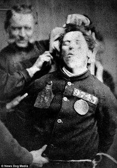 A picture of a man being restrained by wardens taken in West Riding Lunatic Asylum