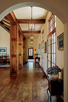 Arched doorways at either end of the front hall add Old World charm to this new home. Dark wood floors gleam underfoot and contrast with the creamy wall color.