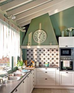 Cocina en tonos verdes y blancos con chimenea de obra